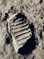 Black and white image of bootprint in Moon dust.